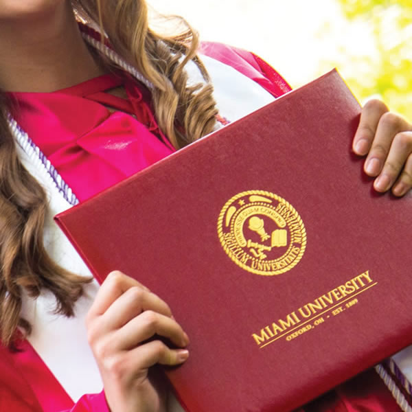 Close up of graduate in robe holding Miami University diploma cover