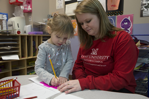 Pre-k student instructor using a stencil with a child.