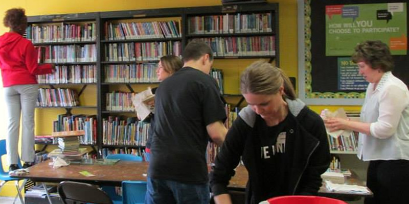 Students and staff cleaning a room with books