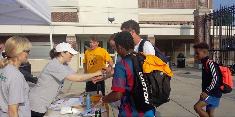 Students registering for the world refugee day cup