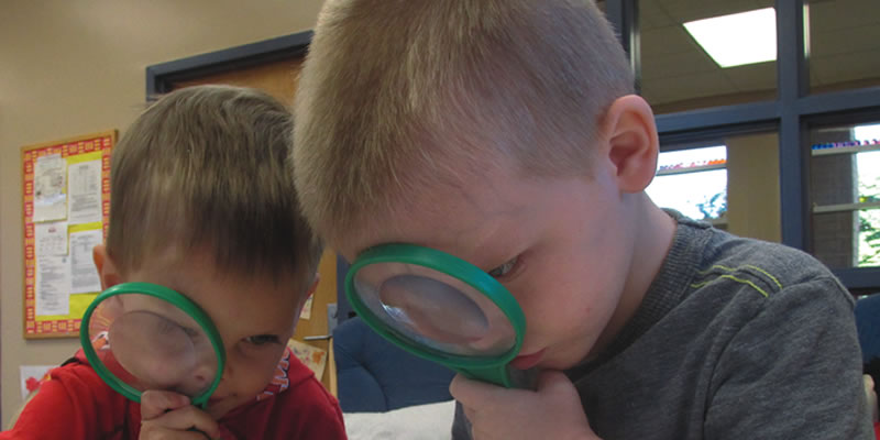 Toddlers with magnifying glasses.