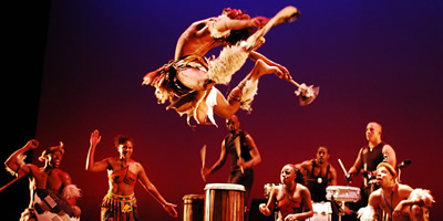 Energentic Step Afrika! dancer leaps high as 7 drummers beat out a rhythm behind him.