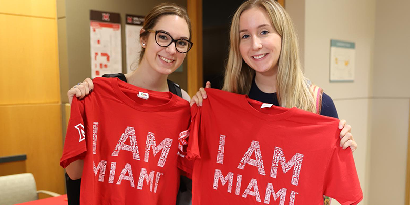 2 Female Students holding up I am Miami T-shirts