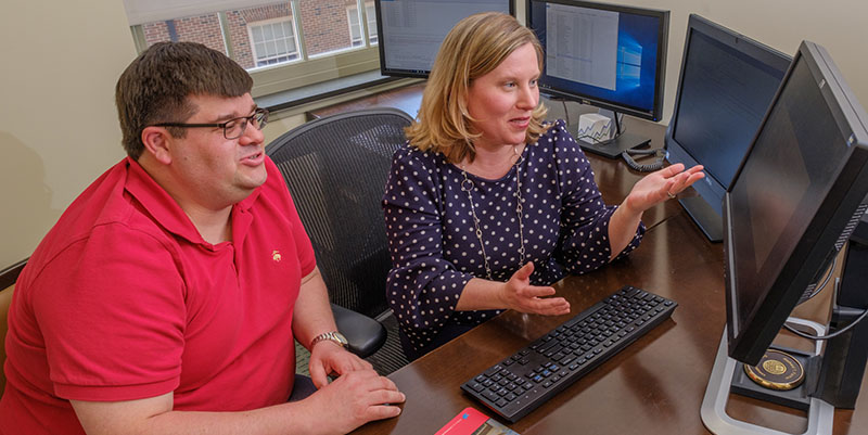 John Bowblis and Amy Roberts sit at a desk on which multiple computers monitors sit. They are looking at one of the monitors and discussing what they see.