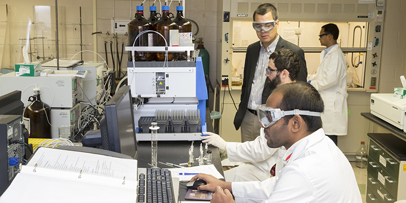 Dr. Scott Hartley and three graduate students work with equipment in Hartley biochemistry lab.