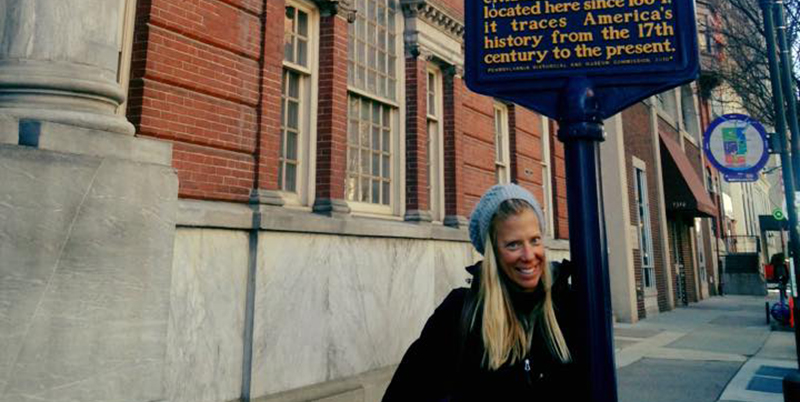 Lindsay Regele stands by a marker commemorating the Historical Society of Pennsylvania. The marker reads: Historical Society of Pennsylvania. Among the oldest of its kind in the nation, the special collections library holds many of the nation