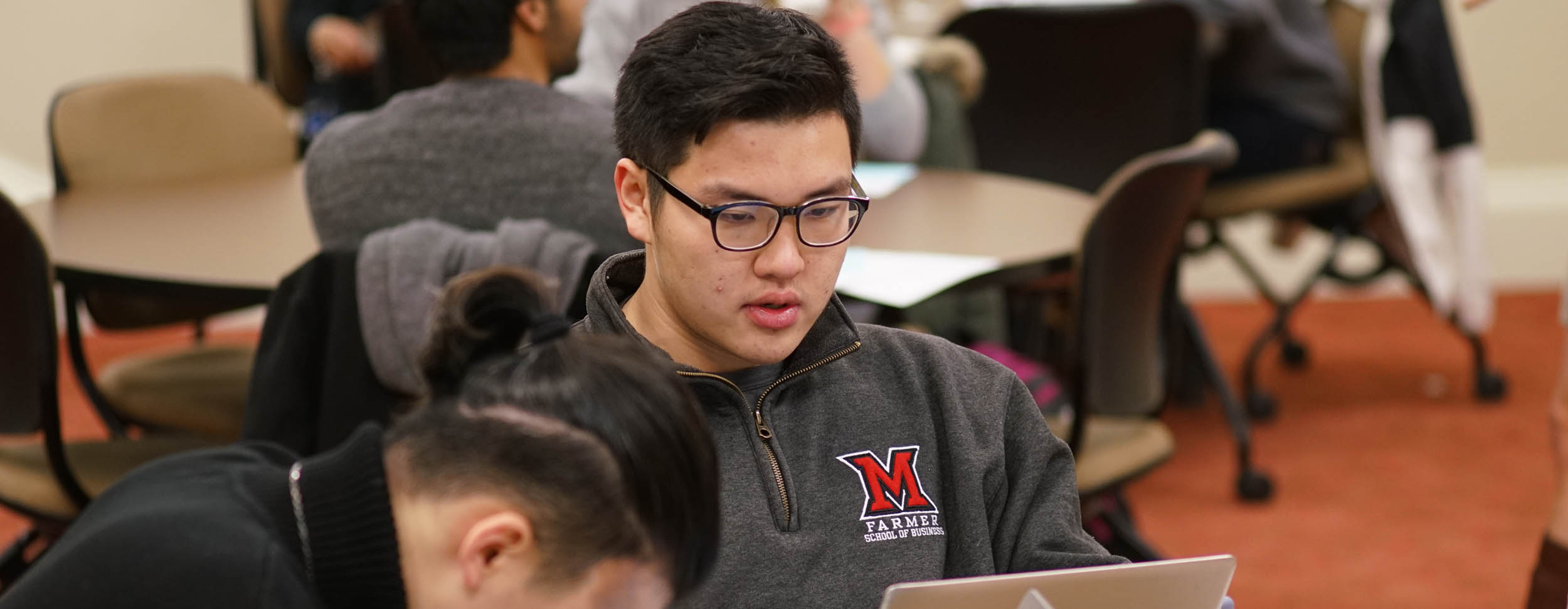 Student looks at his laptop during class